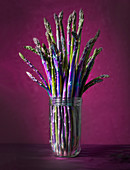 Fresh asparagus spears in a glass against a red-violet background