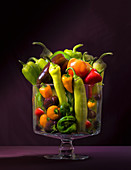 Different types of peppers in a glass jar against a dark background