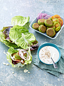 Herb falafel with tomatoes and onions in lettuce leaves
