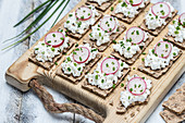 Slices of crispbread with cottage cheese and radishes on a wooden board