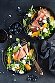 Salat mit Rucola, Blaubeeren, Feta, Parmaschinken und Orange