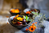 Plums and marigolds in bowl