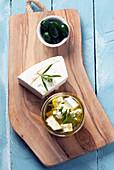 In Olivenöl eingelegter Feta, Oliven und frischer Feta auf Holzbrett