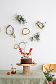 Chocolate cake with physalis garland in front of handmade wreaths on wall
