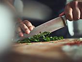 Frische Kräuter mit dem Messer klein hacken
