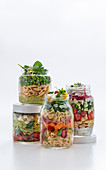 Vier sommerliche Nudelsalate in Gläsern zum Mitnehmen