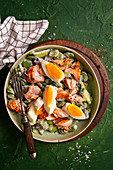 Salad with broad beans, cucumber, olives, salmon, egg and Greek yoghurt dressing