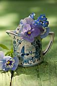 Blüten von Hornveilchen und Vergißmeinnicht in Keramikkännchen
