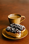 Coconut eclairs and cup of coffee