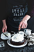 Man preparing chocolate cake with bananas and cream