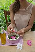 Malvenbreiumschlag zubereiten: Malvenblätter und Malvenblüten in eine Schale geben