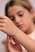 Girl tying friendship bracelet