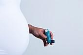 Pregnant woman holding asthma inhaler