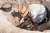 Archaeologist uncovering artefacts