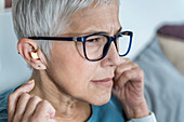 Mature woman using earplugs for sleeping