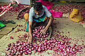 A vendor selling red onions at a market in Sri Lanka
