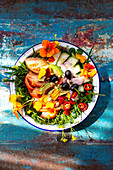 Summer salad with tomatoes, cucumber, chilli, olives and edible flowers