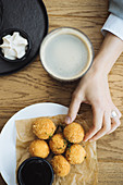 Hand taking tasty potato croquette from plate while sitting at wooden table with hot drink