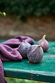 Figs and purple linen napkin on turquoise wooden table