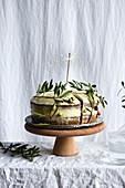 Karottenkuchen dekoriert mit Olivenzweigen und Wunderkerze