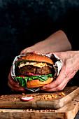 Hands holding a vegan lentil burger