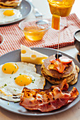 Fried eggs with cheese and bacon and pancakes with berries and honey on table for breakfast