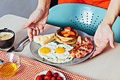 Hands putting plates with delicious fried eggs with bacon and cheese on table for breakfast