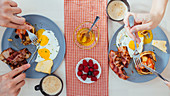 Eating tasty fried eggs with cheese and bacon and pancakes with berries for breakfast at home