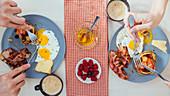 Frühstück mit Pancakes, Spiegeleiern, Bacon und Käse