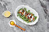 Salad with green beans and nuts on marble table