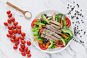 Sliced steak on pile of salad with avocado and tomatoes garnished with shopped onion