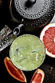 Cocktail mit Eiswürfeln, Tee und rosa Grapefruit