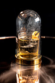 Rauchender Cocktail unter Glashaube auf spiegelndem Untergrund