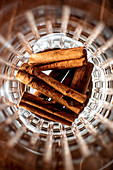Top view of pile of aromatic cinnamon sticks placed inside glass cup in bar
