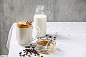 Dalgona Coffee (aufgeschlagener Instantkaffee) mit Zutaten auf Tisch