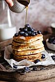 Ein Stapel Pancakes mit Blaubeeren und Sirup