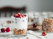 Fermented probiotic kefir or yogurt in glass with granola at the bottom served fresh sweet cherry halves