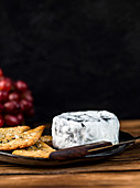 Ashed Brie served with crackers and brie on a wooden background