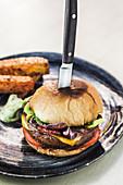 Classic delicious cheeseburger with meat patty served on plate with knife