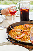 Pan with arroz marinero served on table with plates and fresh drinks