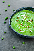 Bowl of freshly made puree of green peas topped with oil and sprouts