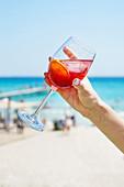 Hand hält Weinglas mit Zitruscocktail am Strand