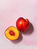 A whole and half nectarine overhead on a textured, pale pink surface
