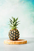 Baby pineapple on a wood board against a pale blue-green background