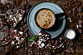 Cup of espresso coffee with jug of milk, handmade dark chocolate, coffee and cocoa beans