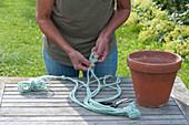 Frau knotet blaue Schnüre für eine Makramee-Ampel