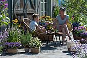Mutter und Sohn sitzen auf insektenfreundlicher Terrasse mit blühendem Basilikum, Scheinsonnenhut, Malve, Fächerblume 'Violet Blue', Zweizahn 'Bee White', Rosmarin