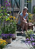 Insektenfreundliche Terrasse mit blühendem Basilikum, Scheinsonnenhut, Malve, Fächerblume 'Violet Blue', Zweizahn 'Bee White', Tagetes, Frau im Sessel