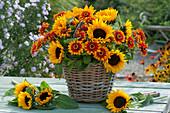 Üppiger Strauß aus Sonnenblumen und Zinnien im Korb