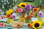 Kleine Sträuße aus Sonnenblumen, Dahlien, Zinnien, Fetthenne und Fencheldolden als Tischdekoration
